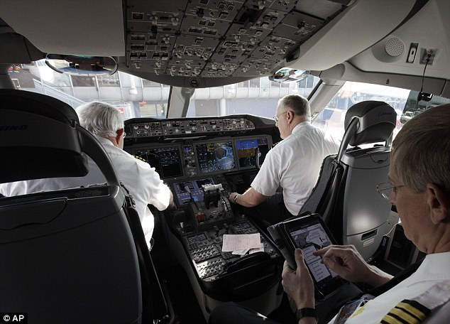 At the helm: Pilots on board the 787 Dreamliner which is touted to be  more fuel efficient than any other similar plane and has a host of passenger amenities, such as larger windows, special lighting and filtered air