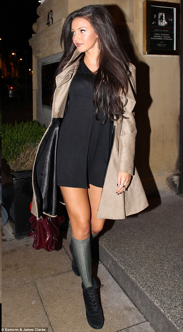 Bare legs: The knee-high socks gave the mini-dress a schoolgirl twist as she went out in Manchester