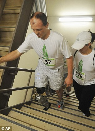 Zac Vawter, left, a 31-year-old amputee, walks up the stairs of the Willis Tower in Chicago on Sunday
