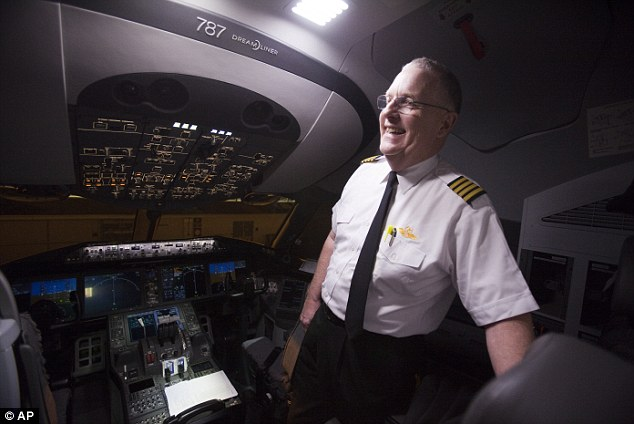 All smiles: First officer, Cpt. Cliff Pittman talks to the media inside the cockpit as United Airlines prepares its first scheduled North American commercial Boeing 787 flight