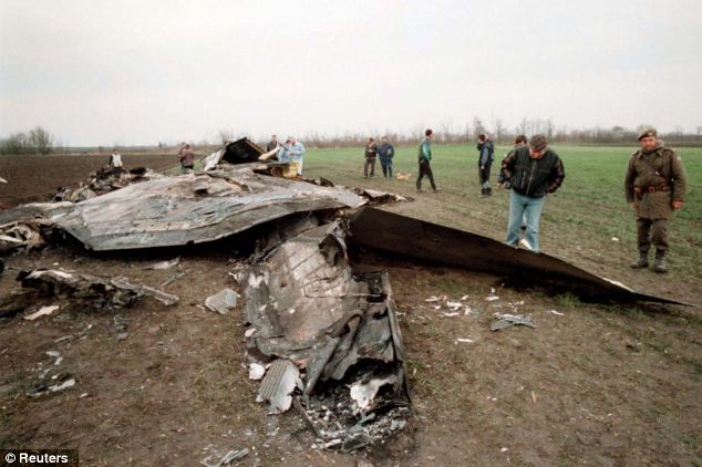 Villagers look at wreckage of the U.S. F-117 Stealth fighter shot down over Serbia during NATO air strikes