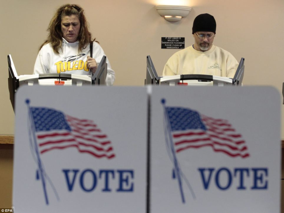 Tough decisions: People vote at a polling site in Toledo, Ohio on Tuesday morning as the men are almost neck and neck in the polls