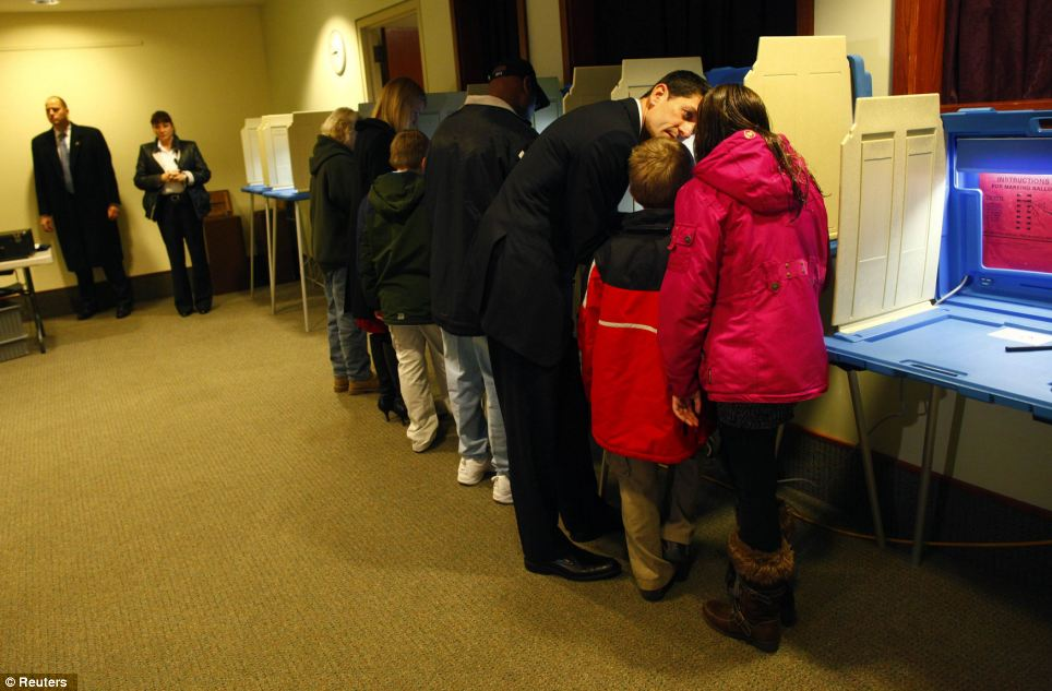 Talking it through: Republican vice presidential candidate Paul Ryan votes accompanied by his children Charlie, Sam and Liza in Janesville, Wisconsin