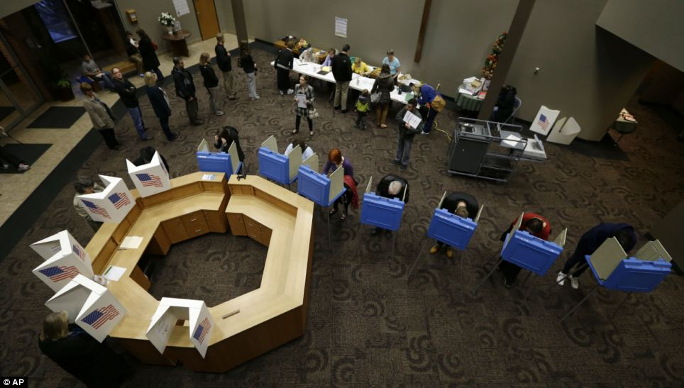 Making a difference: Voters fill out their ballots at the First Church of the Open Bible in Des Moines, Iowa