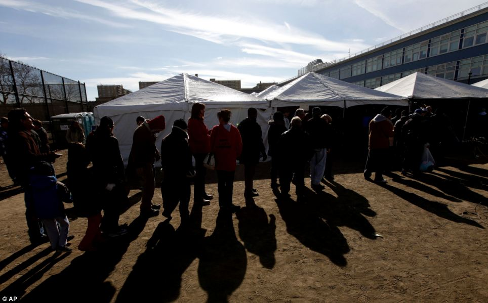 No stopping them: Voters wait in line to cast their ballots under a tent in the Rockaways in New York, which was hit hard by Hurricane Sandy