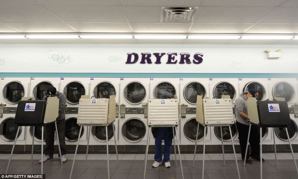 Creative: People cast their ballot at a polling station in a laundromat in Chicago, Illinois as Romney and Obama battle for the presidency