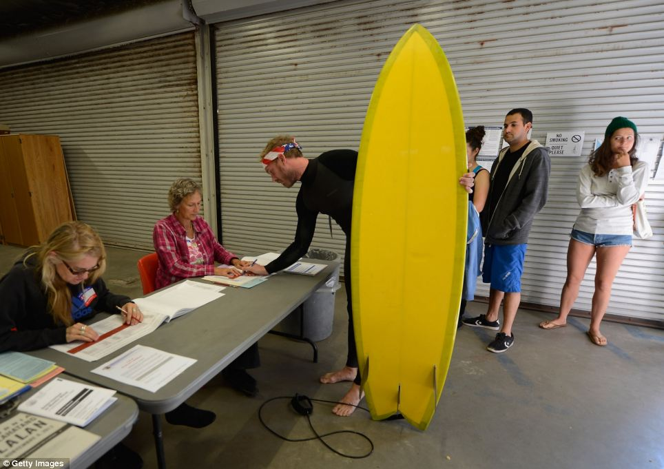 A world away: Mike Wigart, 30, picks up his ballot at a polling station in the garage of the Los Angeles County lifeguard headquarters