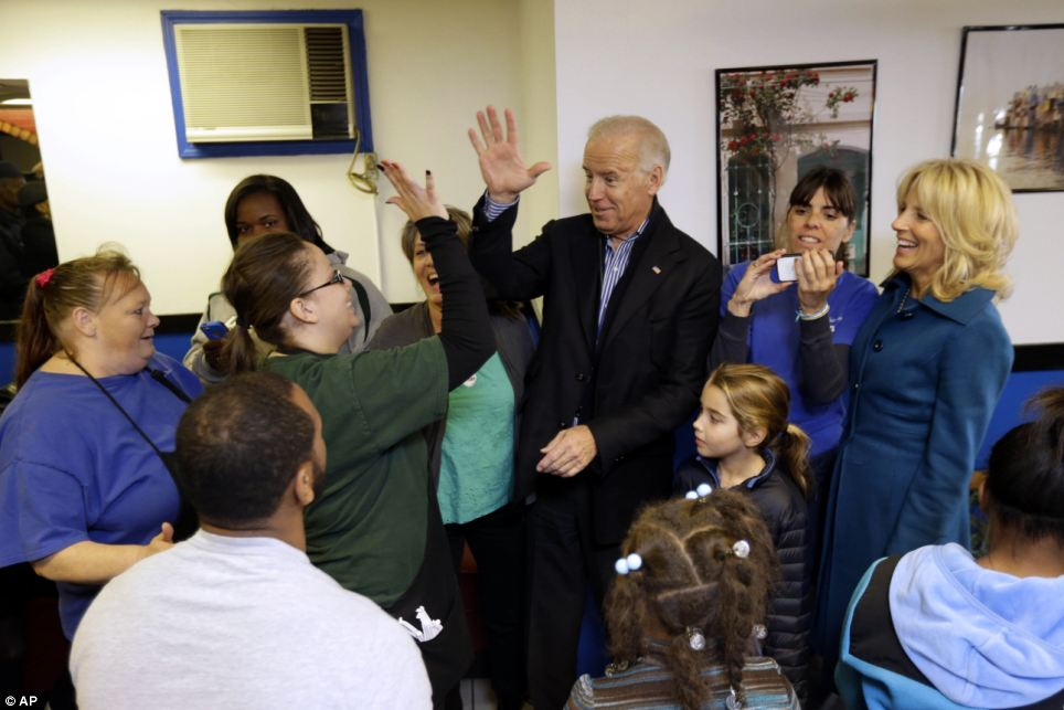 Getting involved: Vice President Joe Biden, with his wife Jill Biden, right, and granddaughter Natalie, meets with patrons during a visit to the Landmark Restaurant in Cleveland, Ohio
