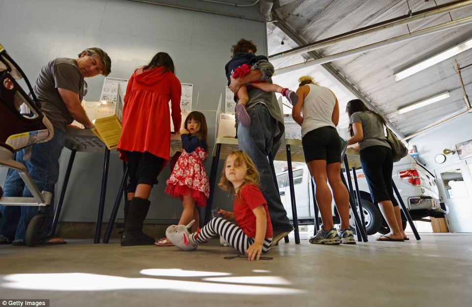 Early voters: Colby Klein, 2, seated on the floor, waits for her parents to cast their ballots in Los Angeles as her sister Astin Klein, 3