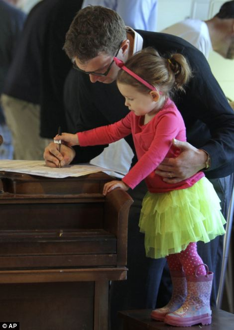 Scott Fera gets help marking his ballot from his daughter, Quinn, 2, while voting in Sacramento, Calif
