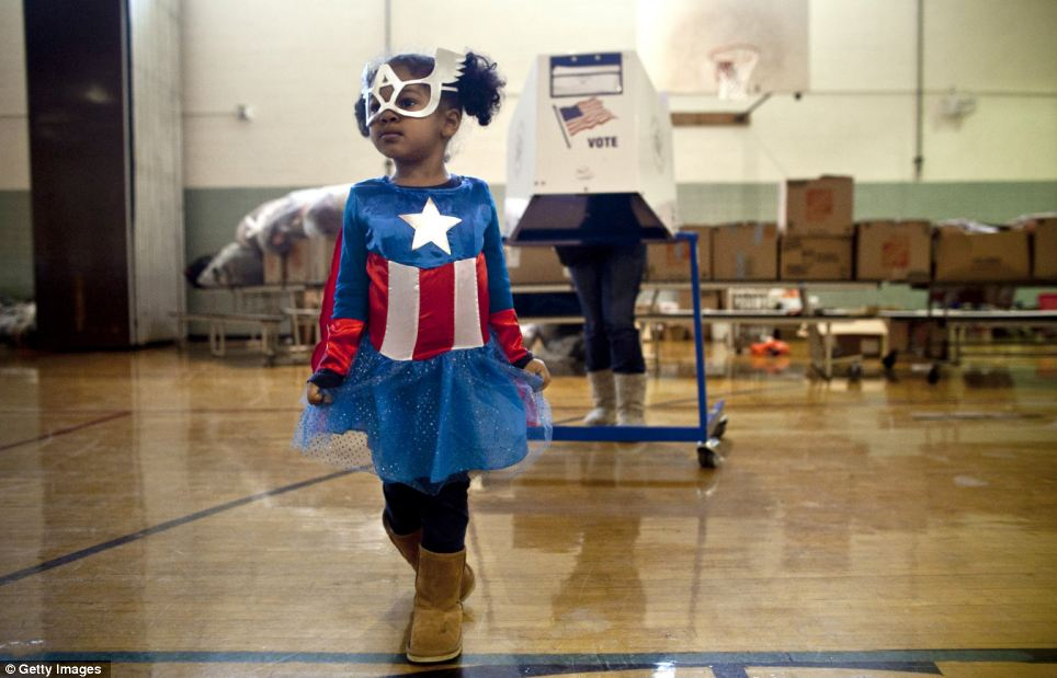 Making a difference: Raena Lamont, 3, wears a Captain America costume at a polling center doubling as a donation site in the Staten Island borough of New York City