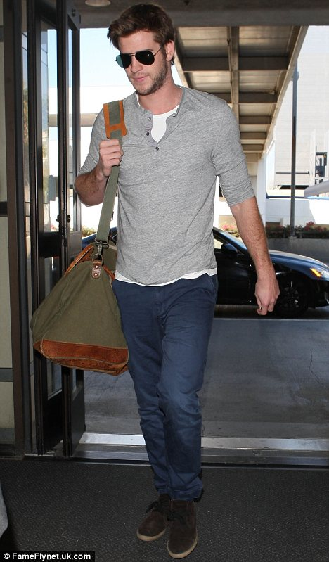 Wandering eye?: Liam Hemsworth, seen jetting out of LA last Tuesday, was reportedly spotted getting 'very cosy' with an attractive blonde at a Hollywood party late last month