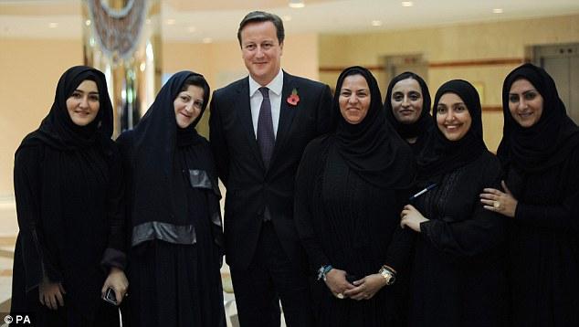 Posing up: Mr Cameron meets female students at Dar Al-Hekma University in Jeddah, Saudi Arabia, on Tuesday