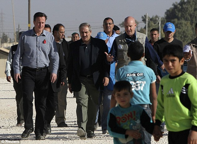 Shocked: Britain's Prime Minister David Cameron (left) walks with Jordanian Foreign Minister Nasser Judeh (centre) during his visit to Za'atri refugee camp in Mafraq, Jordan, near the border with Syria on Wednesday