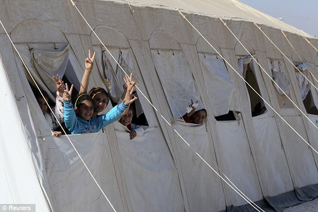 Warm welcome: Syrian school girls cheer during Mr Cameron's visit to Za'atri refugee camp on Wednesday