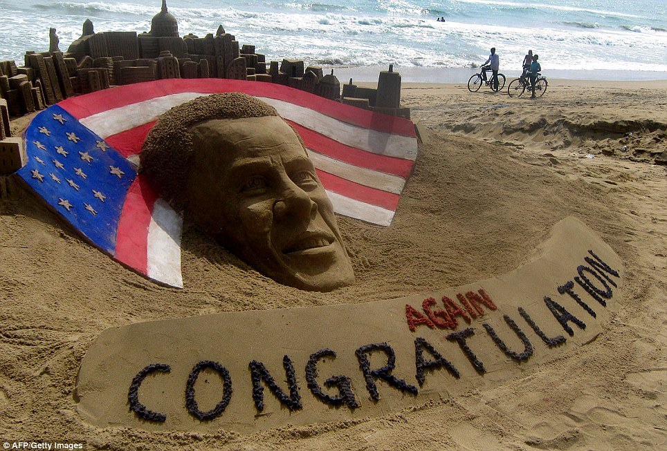 Impressive creation: Cyclists look at a sand sculpture of President Obama by sand artist Sudarshan Pattnaik at Puri beach, east of Bhubaneswar, India, on Wednesday