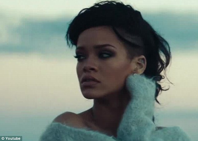 Wistful: Rihanna gazes out over the dry oasis in this scene of her music video with a twinge of sadness