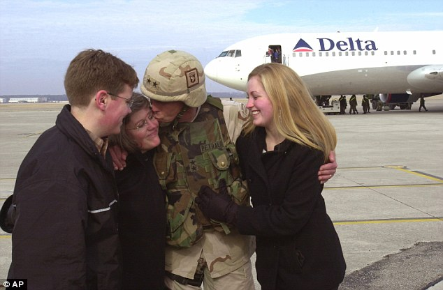 Family Man: In a photograph from 2004 David Petraeus, (center), commanding general of the 101st Airborne Division, kisses his wife, Holly, (second left), as his son, Stephen, (left), and daughter, (Anne), right, look on