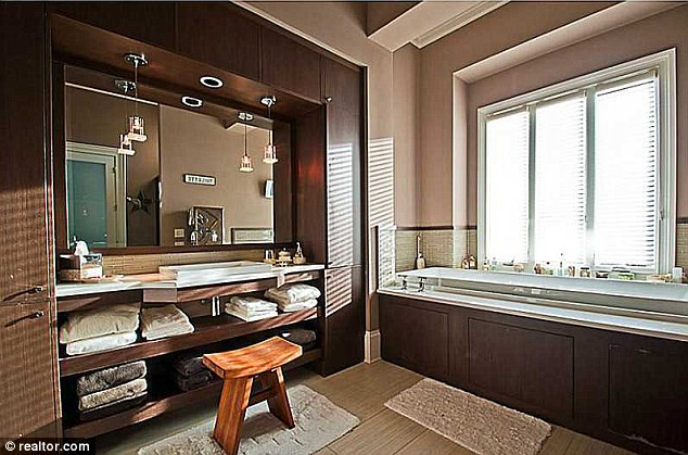 Luxurious: One of the seven bathrooms has a wood flooring a large bathtub and is painted with a calm colour scheme