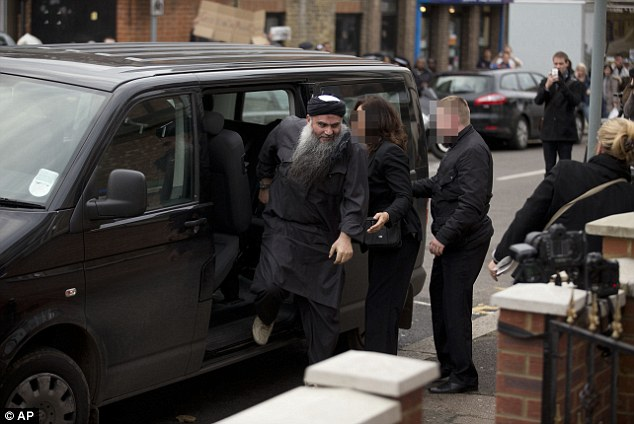 Welcome home: Abu Qatada (left) gets out of the rear of a vehicle as he returns to his residence in London