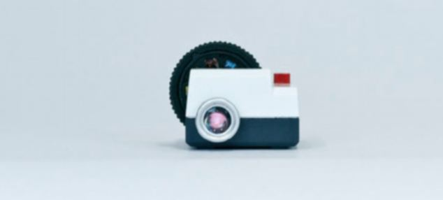 The projector is designed to look like a retro slide proctor, complete with slide carousel