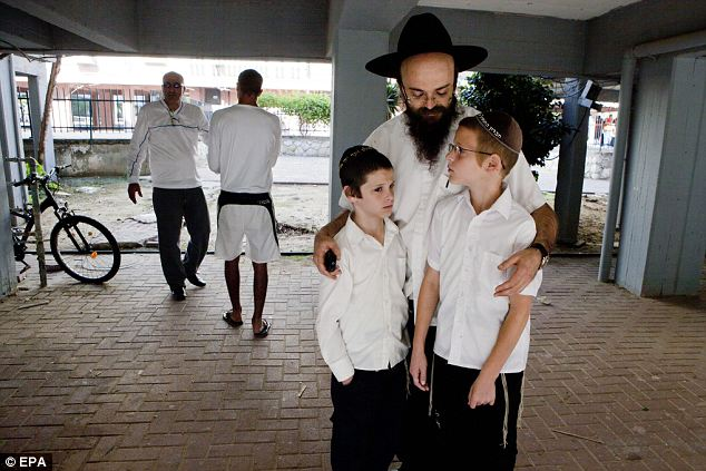 Fatherly love: An Israeli with his two sons as they pray under a protective area during a missile alert