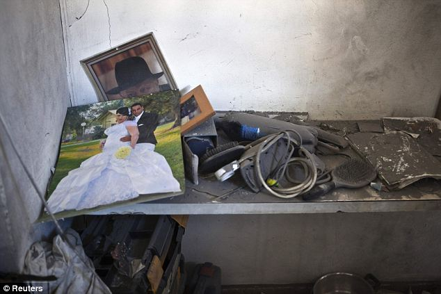 Chilling: A wedding photo and other belongings are seen in a house damaged in the attack