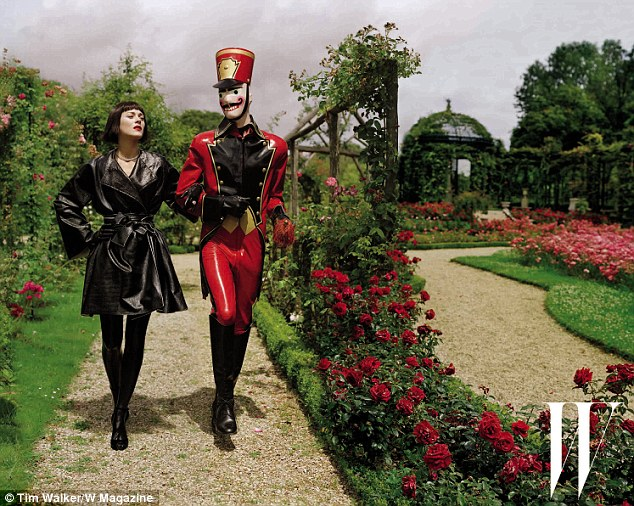 A walk in the park: Marion slips on a coated Lanvin cotton coat as she and her latex soldier take a stroll through a rose garden