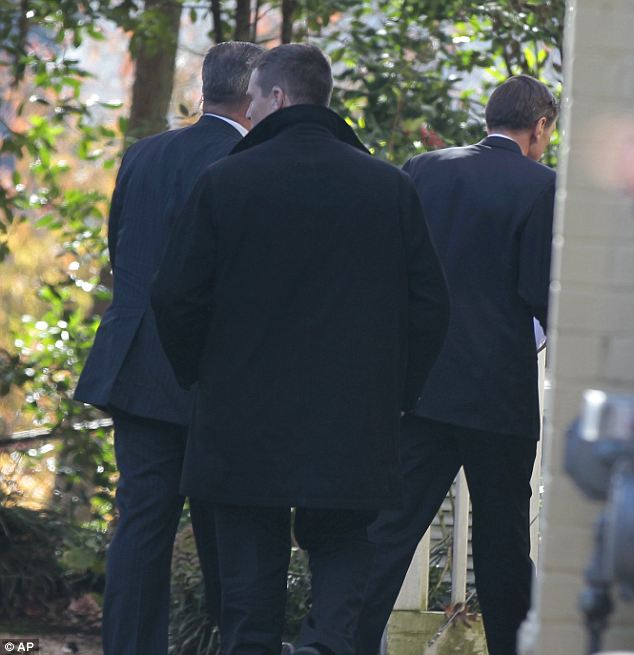 The only glimpse media got of Petraeus, right, followed by security agents, was as he entered his home in Arlington Friday afternoon