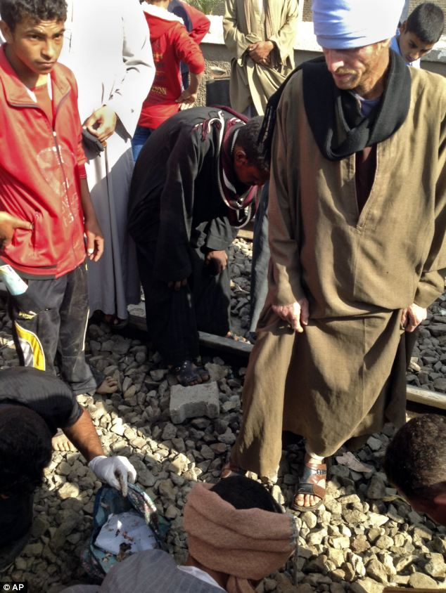 People gather belongings and body parts at the scene of the Egyptian train crash that killed 50 people