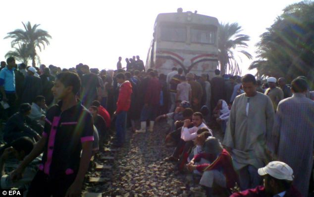 People stand on train tracks in the chaotic aftermath of the train and bus collision in Assiut Province