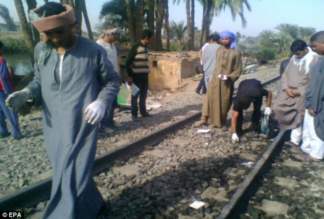 People inspect the site of the horrific crash in the Assiut province, about 190 miles south of Cairo