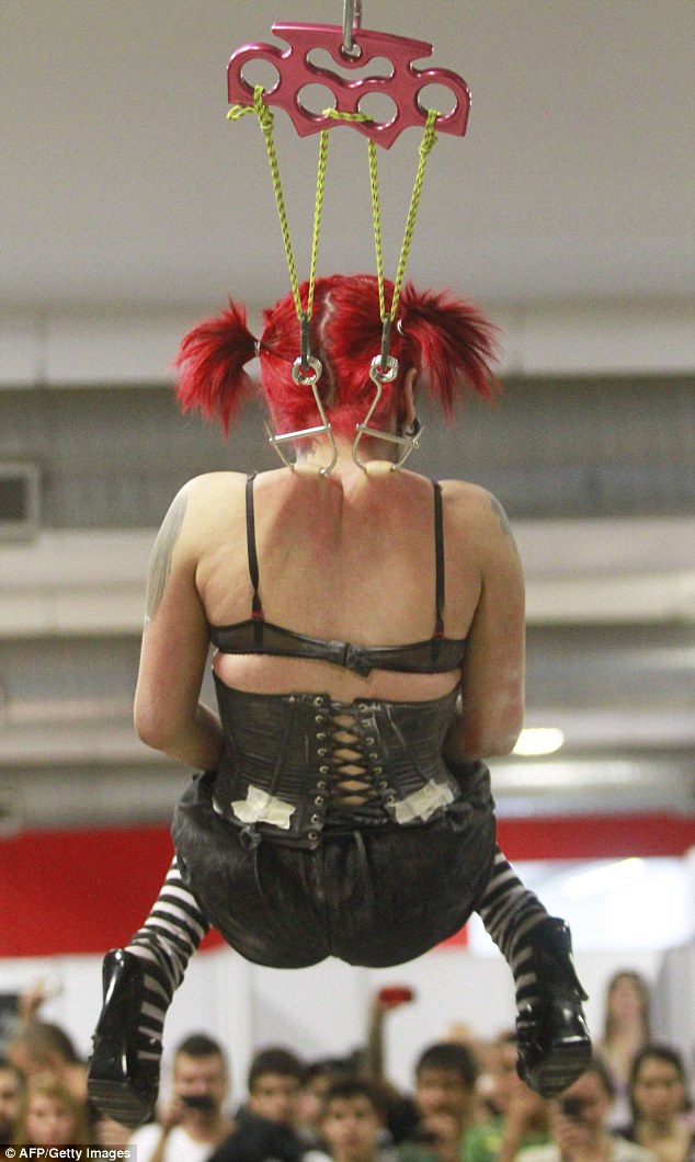 Ouch: A woman is suspended on hooks pierced through the skin during the International Tattoo Convention in Medellin