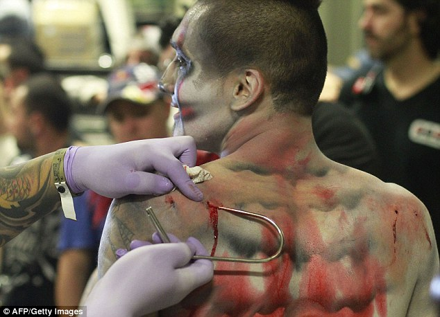 On tenterhooks: One of the entrants into the International Tattoo Convention has a metal hooks taken out of his back