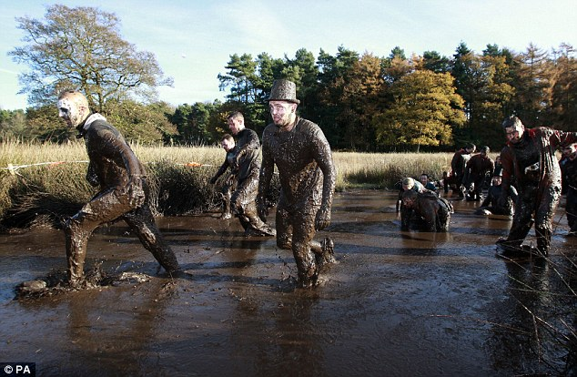 Muddy ridiculous: Competitors make their way through Kiss of Mud 2, during the grueling 12 mile course designed by Special Forces