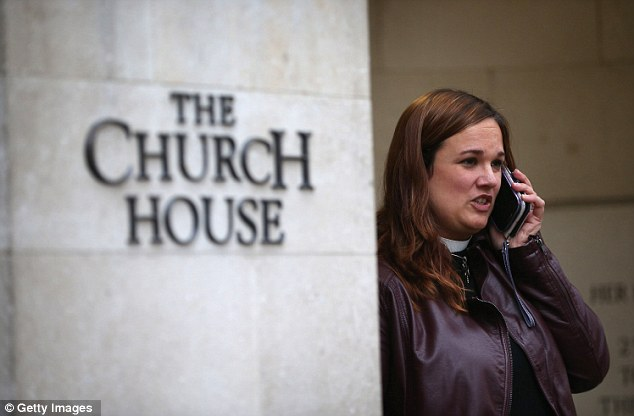 Hope: A female member of the clergy talks on the phone outside Church House just before the vote