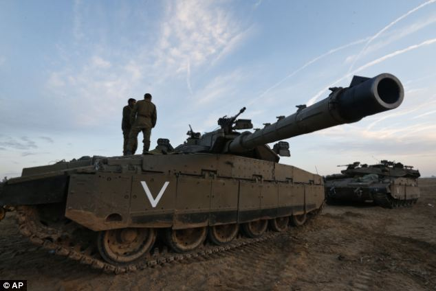 Israeli soldiers talk on top of a tank at a staging area near the Israel Gaza Strip Border, southern Israel