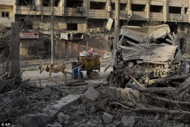 A Palestinian man rides past a destroyed area after an Israeli airstrike at a nearby Hamas government complex known as Abu Khadra in Gaza City