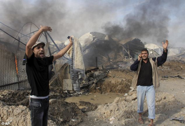 Defiant: Palestinians react as flames and smoke rise from a smuggling tunnel after an Israeli strike