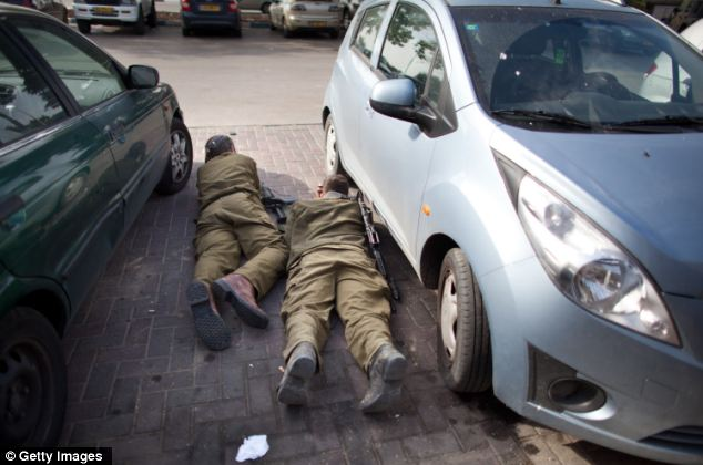 Israeli soldiers take cover during a rocket attack from the Gaza Strip