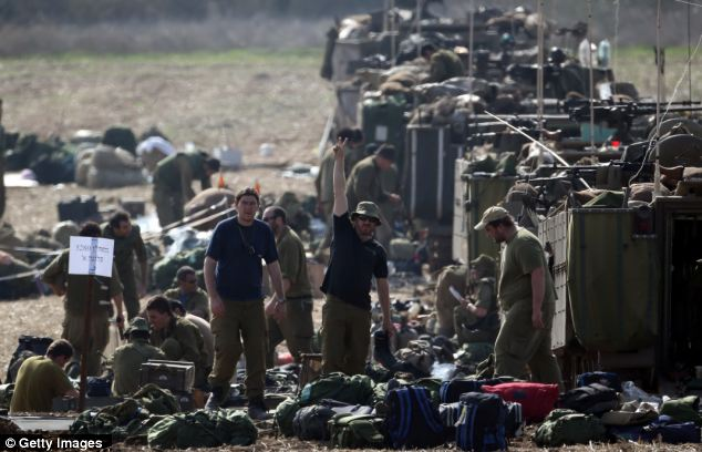 An Israeli soldier gives the victory sign as mechanised infantry check their equipment in a forward staging area
