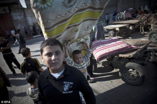 A Palestinian boy carries a mattress to a United Nations-run school in the Jabalya refugee camp, north of Gaza City