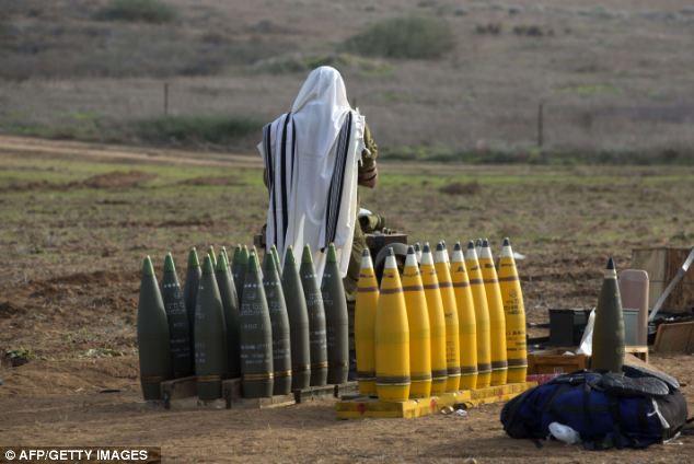An Israeli soldier perform morning prayers at an artillery battery deployment near the Israel-Gaza Strip border