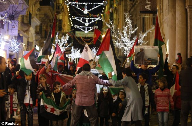 Palestinians living in Malta walk down the Christmas-decorated main shopping centre of Valletta, during a protest against Israeli military action in Gaza