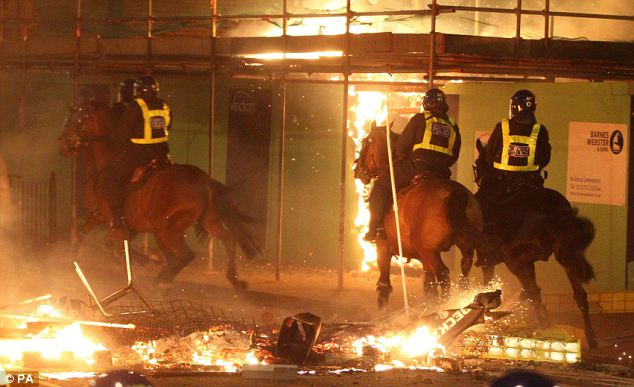 Feeling the heat: A mounted police patrol races through the streets in Tottenham during the riots in August last year