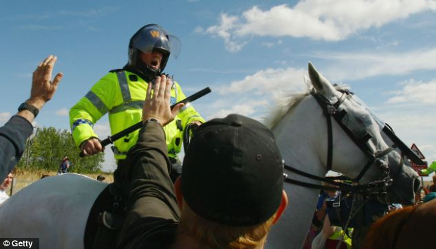 A mounted police officer raises his baton amongst protestors during at Kingsnorth power station in 2008.