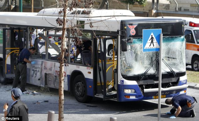 Attack: Israeli police survey the scene after an explosion on a bus in Tel Aviv yesterday