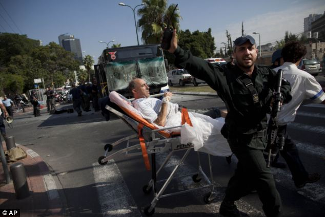 Injured: Israeli rescue workers and paramedics carry a wounded person from the site of a bombing. Police are clearing the area, and early reports suggest it appears there was a second bomb that was not detonated