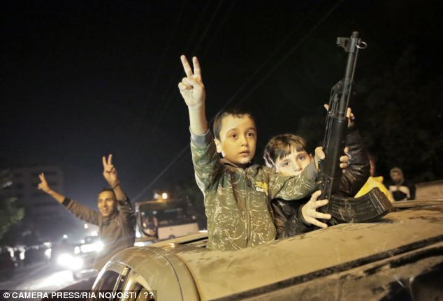 Playing with fire: Two children grip a gun while making victory signs in Gaza