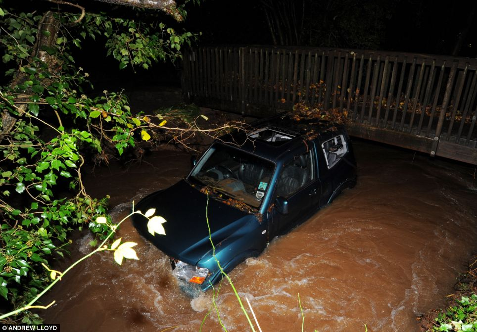 Tragedy: A man died after his 4x4 was washed down a stream by flood water and wedged against a foot bridge in Chew Stoke near Bristol